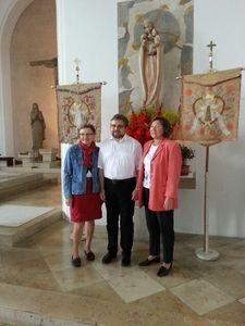 Frau Waltraud Bertossi, Pfarrer Ralf Gössl und Frau Erna Königer (von links) vor den restaurierten Kirchenfahnen.